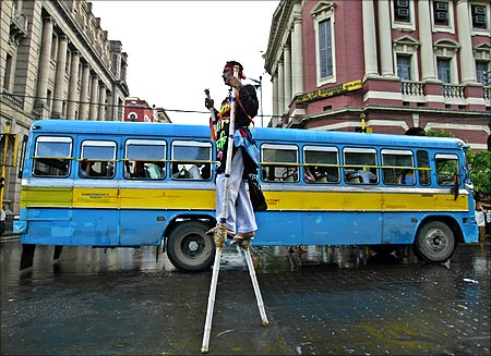 Bablu Das, walks on stilts for an advertisement campaign of an up-coming tourism fair in Kolkata.