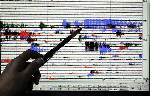 A staff at the National System of Territorial Studies (SNET) points at a screen showing brief quakes.