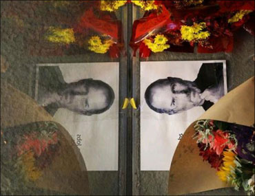 Flowers and a photograph of Steve Jobs are placed against the window outside the Apple store in Boston, Massachusetts.