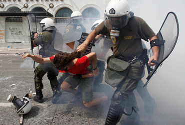 Policemen drag a protestor in Athens, Greece.