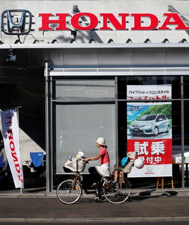 A woman cycles past a Honda dealer in Kawasaki, south of Tokyo