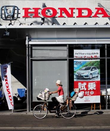 A woman cycles past a Honda dealer in Kawasaki, south of Tokyo