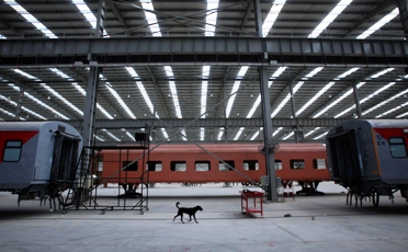 A dog walks past unfinished rail bogies in a rail coach factory in Rae Bareilly.
