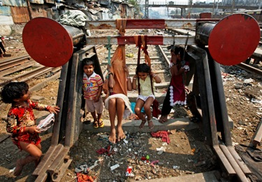 Children play on improvised swings made of cloth hung from a buffer stop near railway tracks in Mumbai.