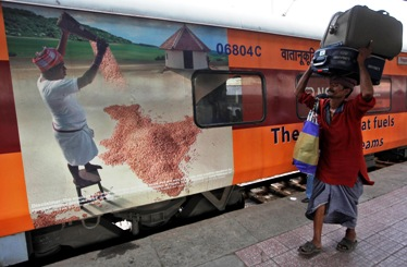 A porter carries luggage of a passenger at a railway station in Kolkata.