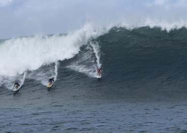 Three surfers catch a large wave in Haleiwa, Hawaii.