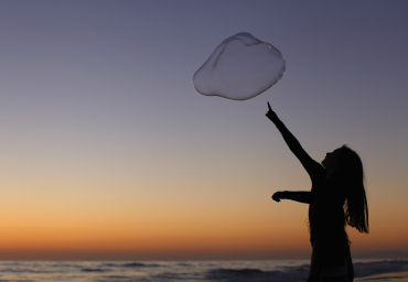 A girl plays with a giant bubble as the sun sets at Moonlight Beach in Encinitas, California.