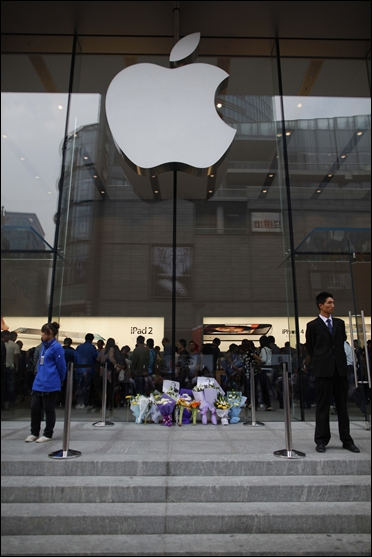 Flowers in memory of Apple co-founder Steve Jobs are placed outside an Apple Store in downtown Shanghai.