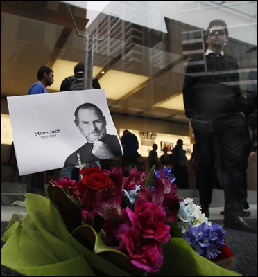 Customers leave an Apple Store as flowers in memory of Apple co-founder Steve Jobs.