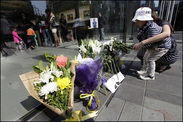 Flowers and a photograph of Steve Jobs are placed against the window outside the Apple store in Boston.