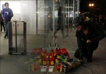 A man leaves flowers outside an Apple store in Boston, Massachusetts.