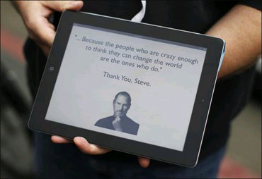 An Apple employee holds an iPad with its screen showing a message in memory of Jobs outside the store in San Francisco, California.