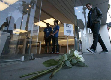 People walk into the Apple Store past roses left for Jobs in Santa Monica, California.