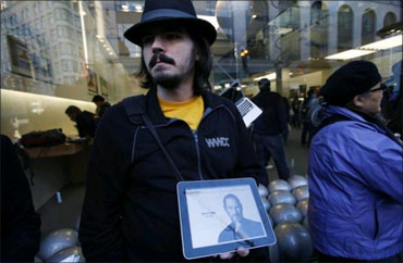 Software developer Steve Streza displays a photograph of Jobs outside the Apple Store in San Francisco, California.