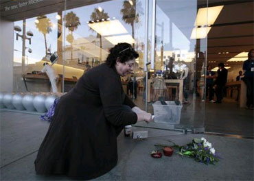 Janine Young, 53, lights an apple-shaped candle for Jobs outside an Apple Store in Santa Monica, California.