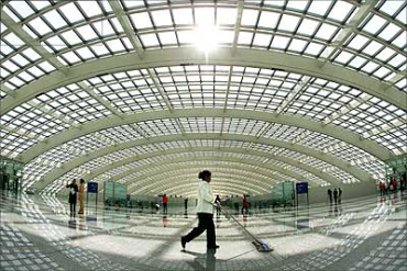 An airport employee cleans the floor at the new terminal building Terminal Three - T3 - at the Beijing Capital International Airport. This is the world's largest terminal.