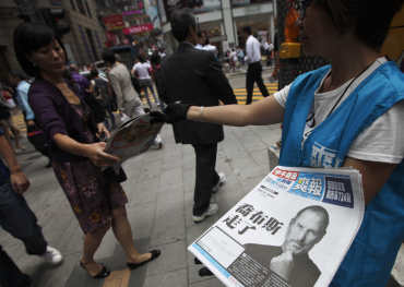 Workers hand out copies of a special edition of the Sharp Daily bearing the headline 'Steve Jobs Passed Away' in Hong Kong.