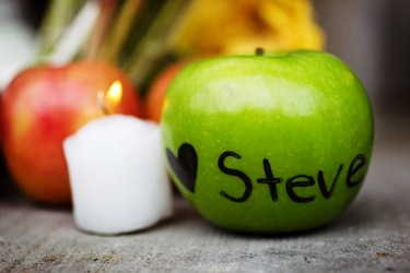 An apple with a heart and Steve Jobs' name written on it is placed in front of a small memorial in San Francisco.