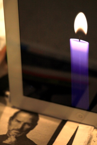 An iPad displays a burning candle in memory of Apple co-founder and former CEO Jobs is placed outside an Apple Store in Hong Kong.