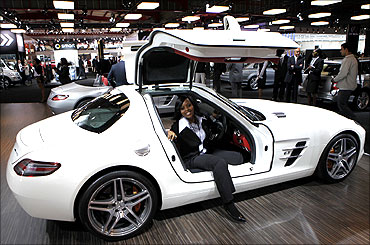 A visitor poses for a photograph in a Mercedes Benz SLS AMG GT3 sports car.