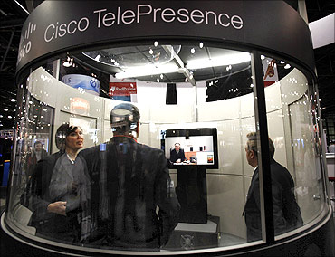People stand inside a Cisco TelePresence conference room at the National Retail Federation Annual Convention.