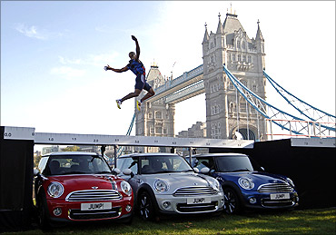 British long jumper J.J. Jegede jumps over three Mini cars, next to Tower Bridge.