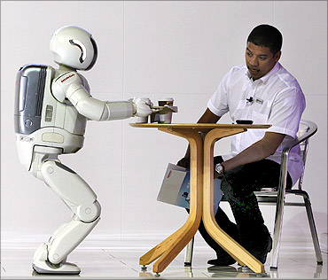 ASIMO, a humanoid robot created by Honda, serves tea to a visitor.