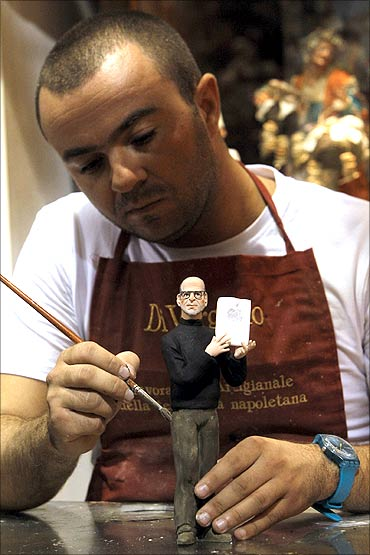 Artist Gennaro Di Virgilio paints a figure of Apple founder Steve Jobs in his shop in Naples.