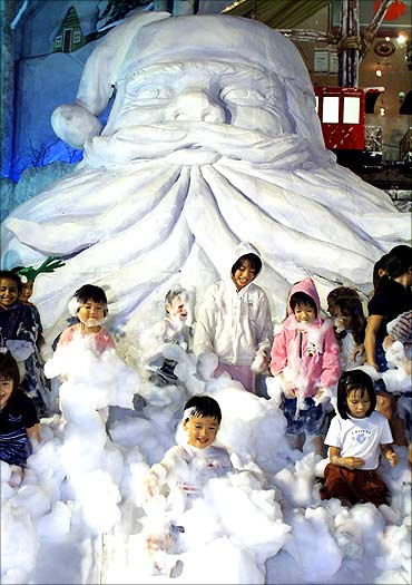 Singaporean children frolic in imitation snow under a giant Santa Claus outside a shopping mall.