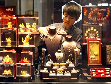 An employee adjusts a gold necklace on a displaying model near glass cases containing gold figurines at a gold shop in Wuhan.