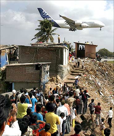 People watch an Airbus A380 aircraft land at Mumbai airport.