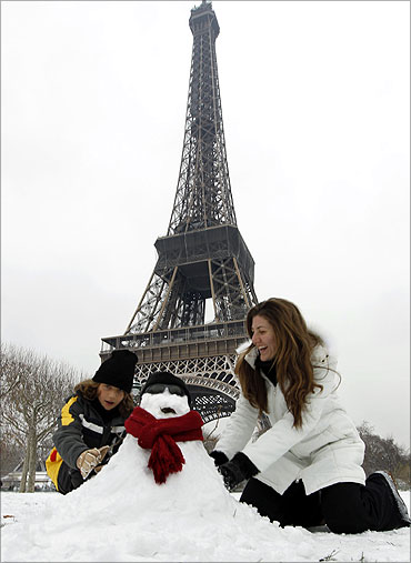 tourists from Sao Paulo enjoy to make a snowman in front the Eiffel Tower in Paris.