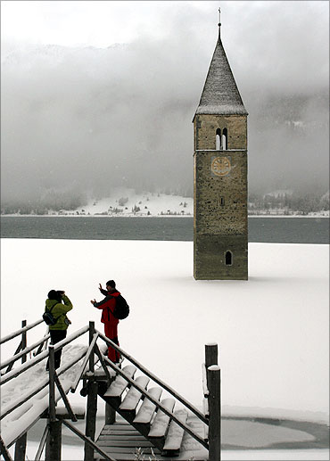 People take pictures in front of the former church tower of the Village of Graun in South Tyrol.