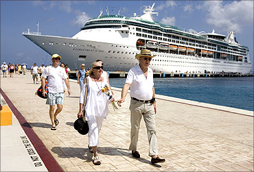 Tourists walk beside Royal Caribbean's cruise ship after they arrive in Cozumel, Mexico.