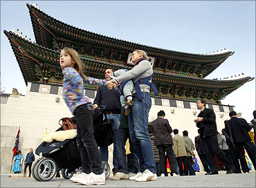 Foreign visitors stand in front of the Gwanghwamun, main gate of the royal Gyeongbok Palace, in Seoul.