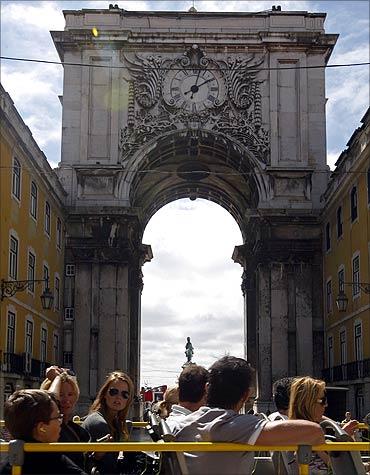 Tourists ride a tourist bus in front of Lisbon's main arcade of Praca do Comercio.