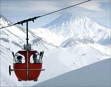 A tele-cabin moves along a rail as Iran's Mount Damavand is seen at the background at Dizin ski slope north of Tehran.