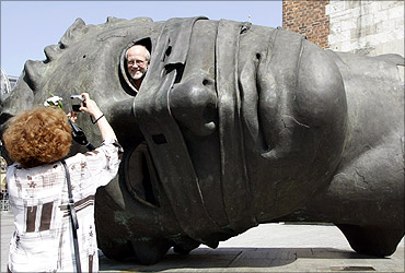 Tourists take a picture with a sculpture by Igor Mitoraj in central Krakow, southern Poland.