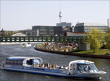 Tourist vessels make their way during a sunny day on the Spree river in Berlin.