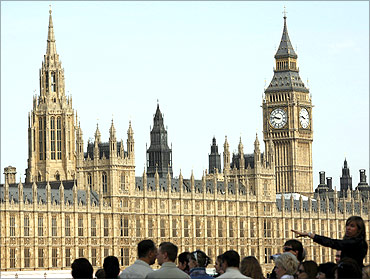 Tourists look at the Houses of Parliament from the south bank of the River Thames, in central London.