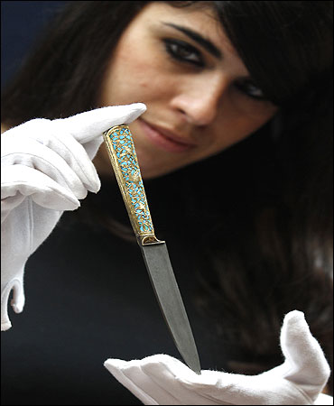 A gold and turquoise-hilted knife.