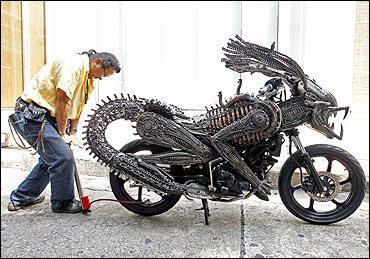 Sangwongprisarn inflates air into the rear tyre of a motorcycle.