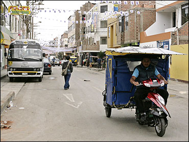 A student test drives a motorised rickshaw running on solar energy on the streets of Lima.