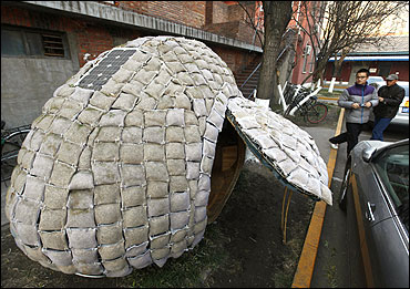 Visitors take photos of an egg-shaped mobile house near its owner Dai Haifei's office building in Beijing.