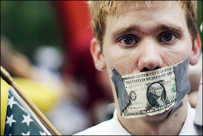 A demonstrator from the Occupy Wall Street campaign stands with a dollar taped over his mouth as he stands in Zucotti Park.
