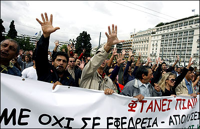 Protesters raise their hands to the parliament in an offensive gesture during an anti-austerity rally in Athens.