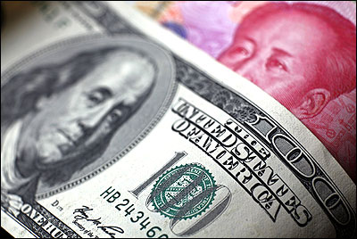 A Chinese 100 yuan banknote is placed under a $100 banknote.