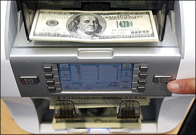 A bank clerk starts a money counter to count 100 dollar banknotes in a bank.