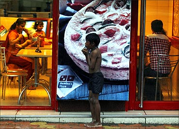 A homeless boy holds biscuits that he received as alms as he takes shelter from rain in front of a fast food shop in Mumbai.