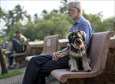 Mohan Silva sits on a park bench in the evening with his eight-month-old specially bred miniature schanuzer, Smokey in Mumbai.